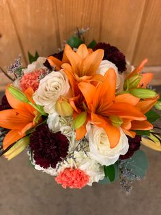 This less is more design has Orange Lilies, White Hydrangea, White Roses, Burgundy Carnations and Orange Carnations.