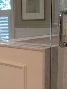 When I design showerstalls I always specify solid slab thresholds and jambs. One of the reasons I often use carrerra marble in bathrooms is because you can find ready-made marble jambs instock at any building centre in one of two materials, carrerra and jura beige. If you go with one of these it means you save the expense and time of having to get jambs custom fabricated from some other material. I prefer classic carrarra so I'll chose counters and tiles that will work with that. Then, splurge o