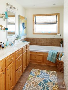Refresh your bathroom without spending a fortune! Check out the simple, inexpensive way this bathroom was refurbished to add major style! Lighter walls, new mirrors and lighting, modern faucets, a subtle wallpaper accent wall, and a colorful piece of artwork are a few of the transformative elements.