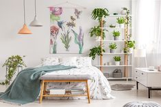 Real photo of white bedroom interior with many fresh plants, king-size bed, material painting with floral pattern and bench with books Emission Deco, Casa Real, Striped Walls, Interior Decorating, Interior Design, Pattern And Decoration, House And Home Magazine, White Bedroom, Sustainable Living