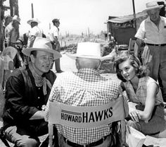 Rare behind the scenes photograph of John Wayne and Angie Dickinson knelt down before director Howard Hawks intently listening to his direction on the set of Rio Bravo (1959).
