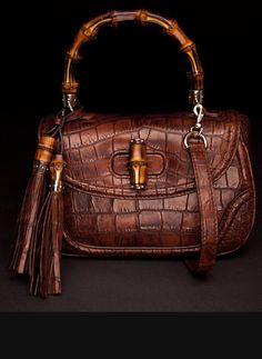 Brown crocodile Gucci purse with bamboo details.