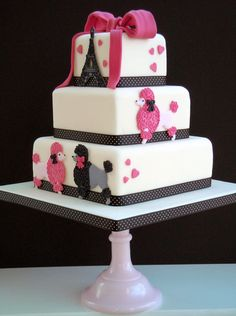 Chic tiered French poodle party cake: Gotta love this gorgeous streamlined cake by Gardeners Delights. Pink hearts, adorable big-haired poodles and the Eiffel Tower, too — ooh la la! The poodles and the tower are made using the ultra talented and cake design queen Peggy Porschen's run-outs designs.