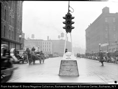 New traffic control at Fitzhugh and Broad Streets.  A horse-drawn wagon approaches the light. Automobiles are parked on both sides of the street. Rochester NY