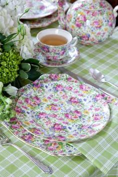 A plaid green tablecloth makes a lively pairing with the lovely floral of the china.