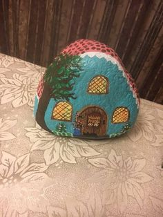 Handpainted garden rock to look like a cottage house. Use it in your home or in the garden to add color. Paint is sealed for outdoor use. Works well as a door stop too