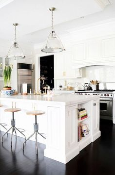 White traditional kitchen with industrial barstools and marble countertop.