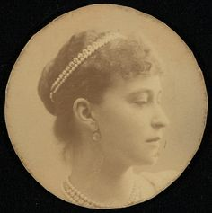 Grã-duquesa Elisabeth Feodorovna em cerca de 1890. Sua cabeça está voltada para a direita e ela está usando fios de pérolas e diamantes ao redor de seu pescoço e em seu cabelo. A fotografia foi cortada em um círculo.