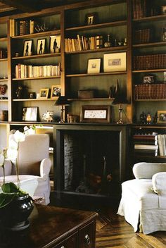 map on one side, bookcase on the other, cozy window seat, leather couch and chair, fireplace for added coziness: this would be my favourite room!