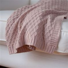 A beautiful reversible knitted blanket/throw in dusky pink. This blanket imbues finesse, luxury and comfort to create a soft furnishing fit for a multitude of surroundings. It looks great casually thrown over the edge of a bed or your sofa. Comes wrapped in a pretty pink bow and makes a lovely gift. 100% Cotton. By Au Maison.