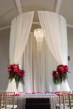 Dramatic draped altar with large floral tie backs. Red and pinks with petals all around.