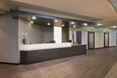 CDH Partners designed a sleek check-in area for WellStar's Kennestone Hospital. The clean lines are created with natural stone, and recessed lighting adds to the elegant decor. Holistic Wellness, Health And Wellness, Health Care, Wellness Studio, Medical Center, Clean Lines, Clinic, Cardio, Stone