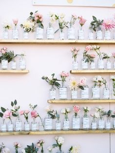 a collection of tea roses in glass perfume bottles