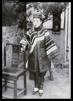 Chinese woman, with bound feet, beside a chair; 1902