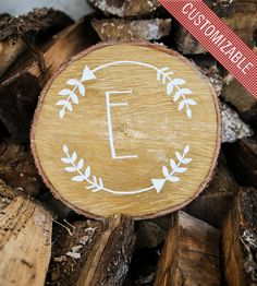 Made from a roughly-cut tree slice, this custom wood art has been hand-painted with metallic gold acrylics and then hand-lettered in white with the initial of your choosing.