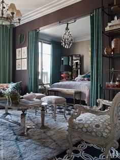 Вид из гостиной на спальню. Комнаты разделяет бархатный занавес с узором из переплетающихся линий. Похожий орнамент украшает также обивку мебели иковер.
