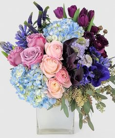 Featuring roses, tulips,and hydrangea in this remarkable arrangement is expertly crafted in soft Shades of Blue , Lavender and Purple. Choose The Premium style designed in a chic custom white glass vase creating an elegant design.