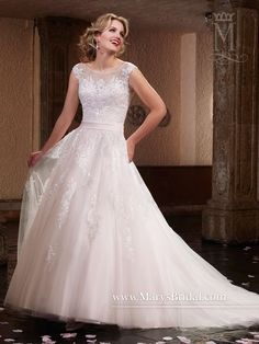 A-line lace and tulle bridal gown with bateau neckline, satin belt, bead embellished bodice, chapel train, back zipper with buttons, and a sheer capelet.