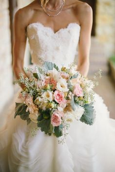 Romantic and rustic pink bridal bouquet and lace wedding dress.