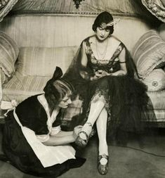 Maid polishing lady's shoe 1921