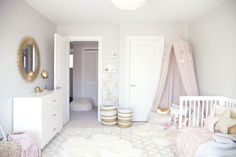 A chic toddler room inspired by Pantone's color of the Year. It pairs rose quartz with gold accents and whimsical details like a play tent and a dress-up corner perfect for a little girl's bedroom.