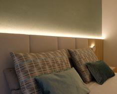 Cabecero a medida realizado en tablero laminado imitación roble y paneles tapizados. Luz trasera que ilumina la pared. Apliques sobre el cabecero para dejar las mesillas libres. Diseño de AZ diseño.