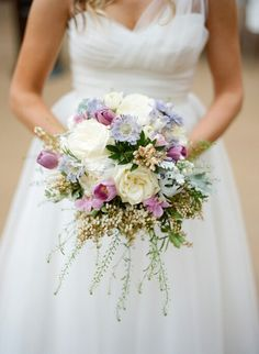 Gorgeous Bridal Bouquet Which Is Arranged With: White Ranunculus, White English Garden Roses, Ivory Lisianthus, Light Blue Scabiosa Flowers, Purple Tulips, Violet Orchids, White Andromeda, + Several Varieties Of Greenery/Foliage·····