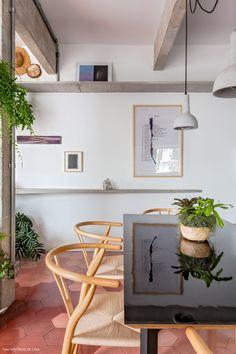 Cadeiras Wishbone e luminária de concreto compõem a decoração dessa sala de jantar.