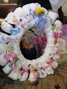 So cute for a baby shower gift! Using a wreath form from Michael's wrap it with diapers and tie each with a rubber band first then to hide the rubber bands attach toys, baby spoons, teethers, socks, a paci, travel-sized toiletries and hair bows with ribbon