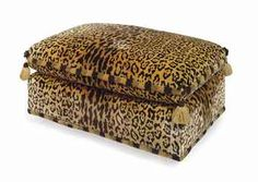 A FAUX LEOPARD PLUSH-UPHOLSTERED OTTOMAN