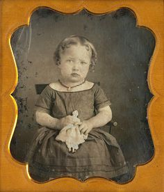 Sweet little girl with doll and ringlets.