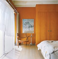 Even in a coastal community, wood paneling does the trick. To keep things from getting heavy, sheer curtains let light and breezes into the master bedroom of this Long Island home. Photo by Richard Foulser.