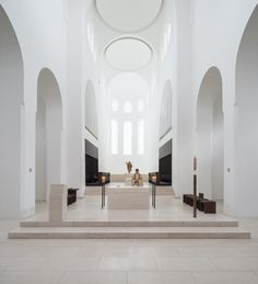 British architect John Pawson's minimalist remodelling of a church in Augsburg, Germany, includes slices of onyx over the windows to diffuse light more softly through the space.