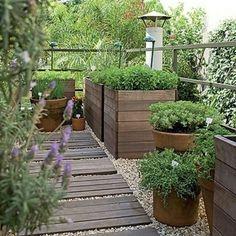 """""""A varanda estreita e pouco aproveitada foi transformada em horta. Os temperos foram dispostos em cachepôs de madeira e pisadas do mesmo material delimitam…"""""""