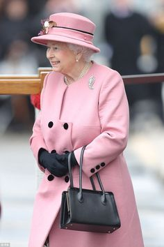 Accessorising her pink collar-less coat with a three-tier string of pearls and matching earrings, the Queen also wore a striking diamond brooch