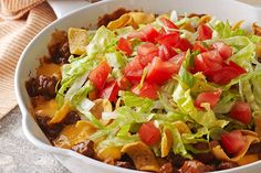 In this easy, cheesy skillet, ground beef is flavoured with onions and taco seasoning mix, then topped with corn chips, VELVEETA, lettuce and tomatoes before serving.