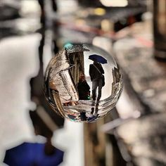 Man with blue umbrella and his reflection. Edited using MarbleCam