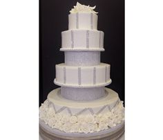 This wedding cake we created for a bride this past weekend is simply stunning, complete with rhinestone tiers and ribbons as well as white sugared roses.