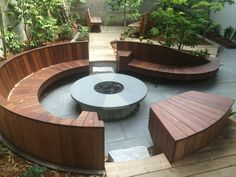 Circular Ipe' bench with built-in desks/arm rests and gas fire pit.