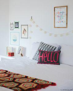 Quarto clean e iluminado com toques de cor em objetos como almofadas e mantas.