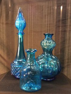 LOVELY VINTAGE BLUE GLASS LIQUOR DECANTERS INCLUDING A STATUE OF LIBERTY CLEVENGER BROS. FLASK. ONE OF THE STOPPERS IS MISSING FROM THE BIGGER DECANTER, SO IT COULD ESSENTIALLY BE USED AS A VASE. THE TALLEST PIECE MEASURES APPROX. 14 IN.