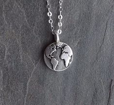 Beautiful tiny silver Earth necklace Wonderful Graduation Gift Earth Globe charm is silver plated pewter, made in the USA. It is tiny -- 12mm in diameter (a tiny bit less than 1/2 inch). It is much smaller than a dime as shown in the last photo for size reference. The chain is sterling silver and shiny and you have a choice of 16 or 18. Please let me know if you need a different length or style. Wear this lovely layering necklace to show your love of the Earth, travel, wandering, and s...