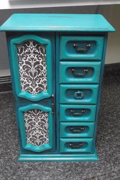 This very large all wood vintage jewelry box has been hand painted inside and out distressed and waxed with a European furniture wax to give you years of durability and enjoyment! French black and white damask decorative paper have been decoupaged to the door. Six large drawers, and hooks for necklaces, and a ring carousel, meet all your storage needs. And these beautiful colors excite the eyes! The dimensions of the Stunner are: 18.5 Tall x 11.5 Wide x 7 Deep