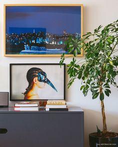 Cantinho da sala de estar com aparador cinza, quadros em tons de azul  e plantas.