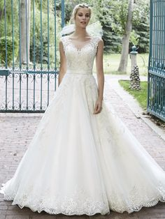 Maggie Sottero - BELLISSIMA, This tulle ball gown is the epitome of bridal bliss. Complete with dazzling Swarovski crystals accenting the bodice and illusion neckline, scalloped lace hemline, and delicate satin belt at the waist. Finished with pearl button over zipper and inner elastic closure.