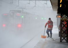 A worker cleans snow off the platform at the Metro North Train station in Greenwich, Conn., on Jan. 23, 2016. IMAGE: TIMOTHY A. CLARY/AFP/GETTY