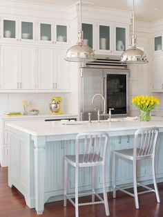 A sea-inspired color scheme of robin's egg blue, warm white, and splashes of contemporary sheen update the look of this classic coastal kitchen. Shaker-style cabinetry and beaded-board panels on the kitchen island blend perfectly into the relaxed setting. The U-shape floor plan is modest in size, making it efficient and comfortably intimate for a couple.
