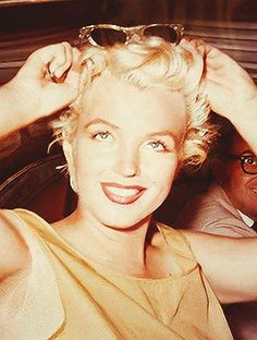 A stunning candid picture of Marilyn wearing fabulous sunglasses possibly taken in 1955.
