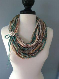 MESCOLATO I COLORI E...Singola maglia infinito sciarpa collana multi colori. Diversi tipi di filati e nastri sono stati utilizzati per creare un look unico. Può essere indossata in vari modi a seconda dello stile che si sta per. Indossarla da sola, o vesti con una spilla fiore, pulsante o gioielli decorativa. Il filato e il nastro utilizzato è una miscela di cotone, lana e acrilico. La sciarpa è circa 46 pollici in giro... lungo abbastanza per indossarlo doppia o tripla avvolto intorno al…