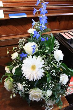 Church wedding Flowers. Small table arrangement of Gerbera, Roses, Carnations, Gypsophila  & Blue Delphinium  at the entrance  to the Church. By H J Strike.